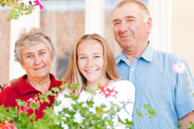 Elderly couple, woman and man with their daughter standing in the middle