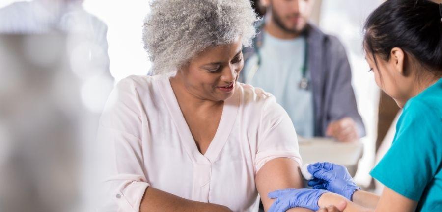 elderly African American woman getting flu vaccine