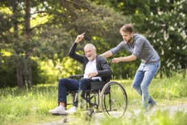 Elderly man on a wheelchair being pushed by a younger man in the middle of a park