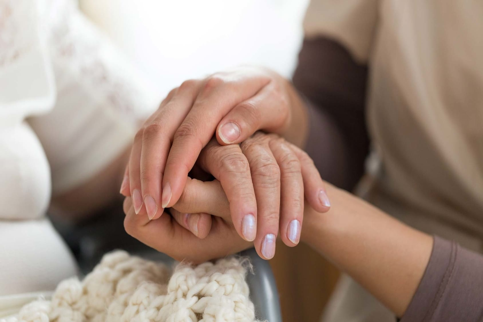 Close up of two women's hands holding each other